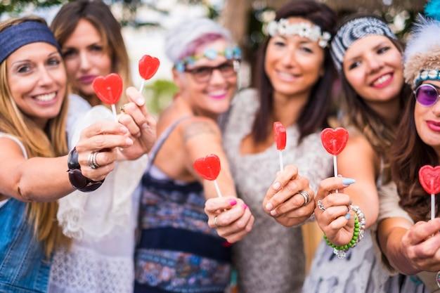 若い人から年配の女性まで、さまざまな年齢の女性のグループが、友情の中で一緒にいて、キャンディーハースのロリポップを取り、提供します
