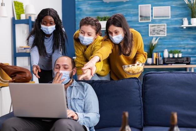 Группа друзей смешанной расы, весело проводящих социальное дистанцирование с помощью маски для лица, предотвращающей распространение коронавируса, потрясенно смотрит на видео на ноутбуке в гостиной, пьет пиво и ест чипсы. conce