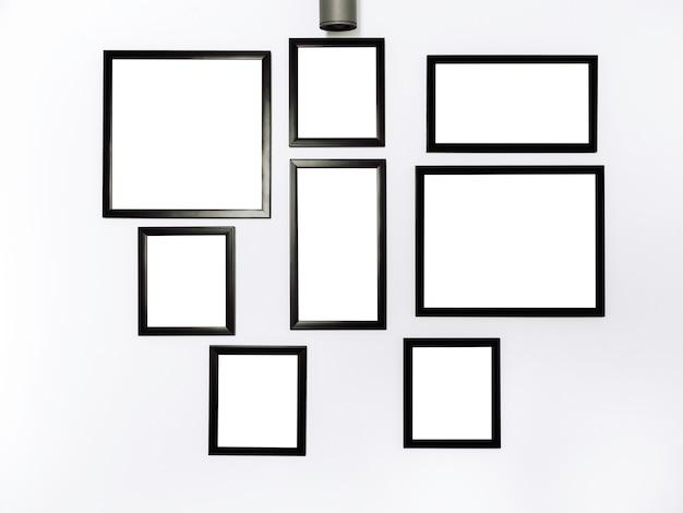 모형 사진 프레임 그룹입니다. 흰색 벽 배경에 검은색 프레임 모형이 매달려 있는 흰색 사각형 그림.