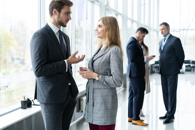 사무실 건물의 햇볕에 쬐 인 유리 홀에 서있는 커피 브레이크 동안 채팅을하는 현대 비즈니스 사람들의 그룹