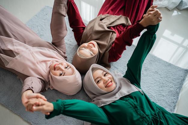 매트리스에 누워있는 동안 회교도 여자 친구의 그룹 미소
