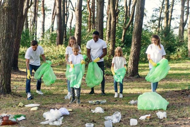 Группа разновозрастных волонтеров сохраняет природу в чистоте и собирает мусор в лесу.
