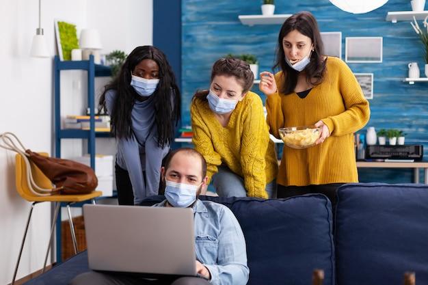Группа многонациональных друзей, сохраняющих социальное дистанцирование в маске для предотвращения распространения коронавируса, смотрит на ноутбук в домашней гостиной, проводит время вместе, пьет пиво и ест чипсы. конц