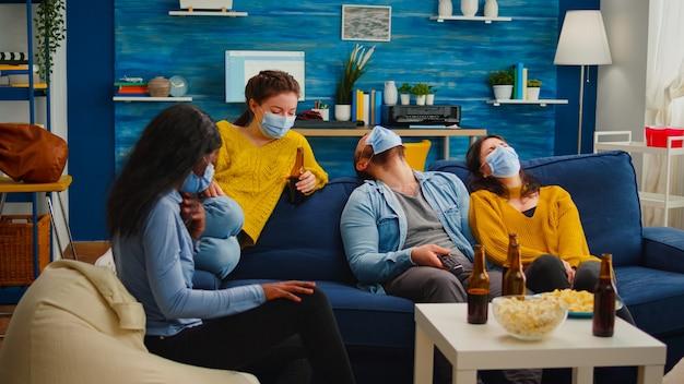 社会的な距離を保ちながらソファに座って楽しんでいる世界的大流行の間に、コメディーショーをテレビで見て笑っている多民族の友人のグループがフェイスマスクを身に着けてcovid19の感染を防ぎます