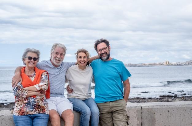 Группа семьи нескольких поколений, сидящих и обнимающихся на море. концепция любви и семьи