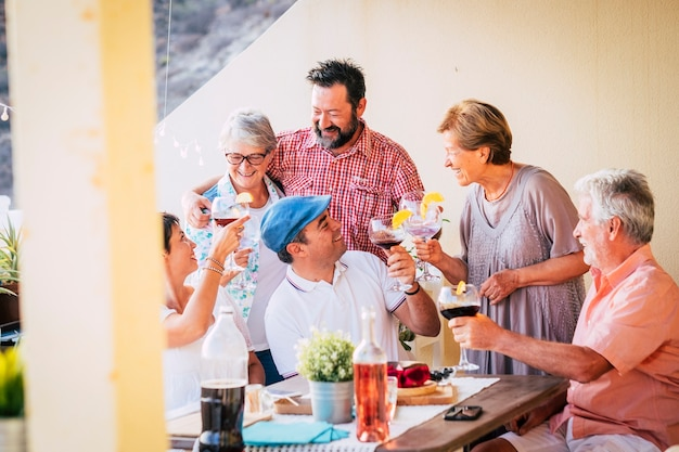 テラスでランチを楽しんでいる多世代の友人や家族のグループ。乾杯用のワイングラスを持っている人々のグループ。食べ物や飲み物を飲みながら祝う家族