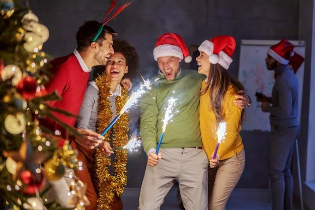 彼らの会社でクリスマスイブを祝う多文化の同僚のグループ。