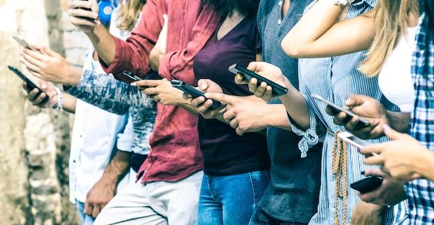 야외에서 스마트 폰을 사용하는 다문화 친구의 그룹-모바일 스마트 폰에 중독 된 사람들의 손-연결된 남성과 여성과 기술 개념-빈티지 필터 톤에 필드의 얕은 깊이