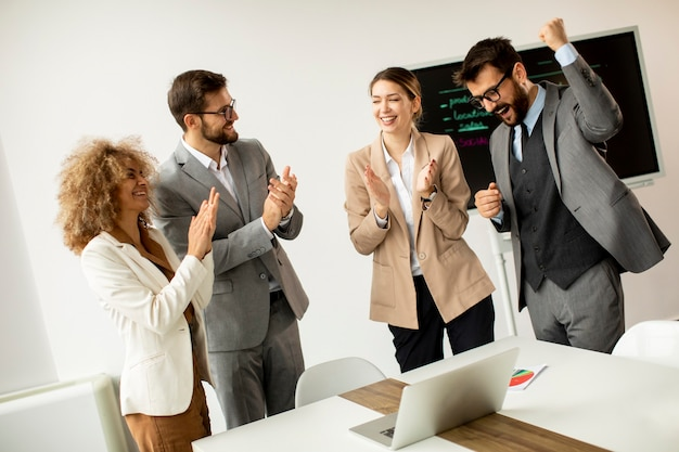 Группа многоэтнических деловых людей аплодирует после успешной встречи в офисе
