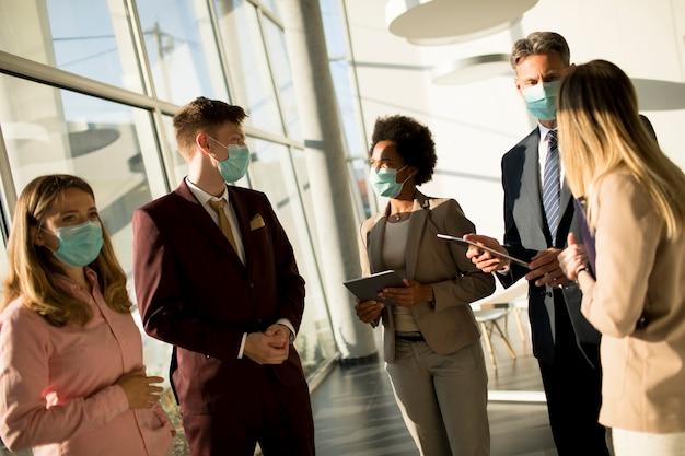 多民族のビジネス人々のグループが会議を行っているし、保護としてマスクを着用しながらオフィスで働いています。