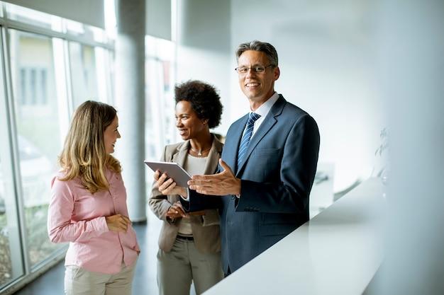 Группа многоэтнических деловых людей, использующих цифровой планшет на встрече в офисе