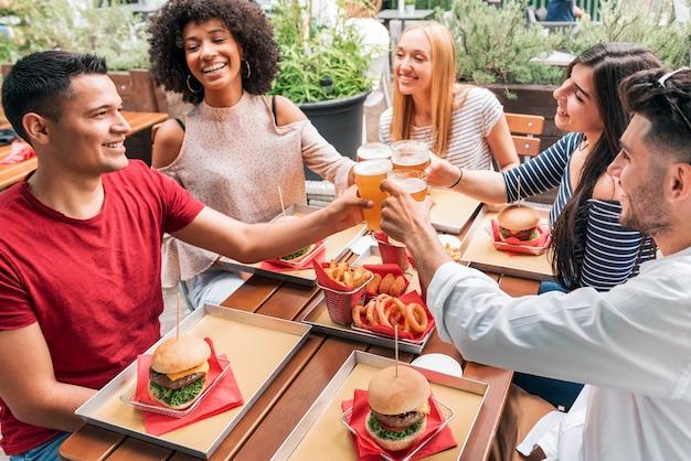 토스트를 제안하고 친구의 생일을 축하하는 동안 패스트 푸드와 맥주 잔으로 테이블에 모인 다민족 쾌활한 친구들