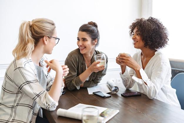 커피숍에서 함께 공부하는 다민족 쾌활한 젊은 여성 그룹