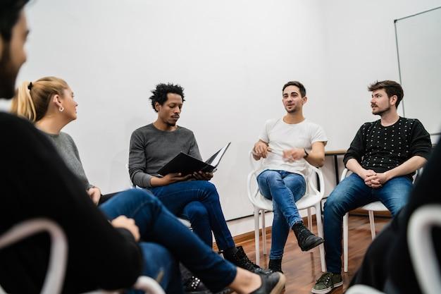 プロジェクトに取り組んでおり、ブレーンストーミング会議を行っている多民族の創造的なビジネスマンのグループ。チームワークとブレーンストーミングのコンセプト。