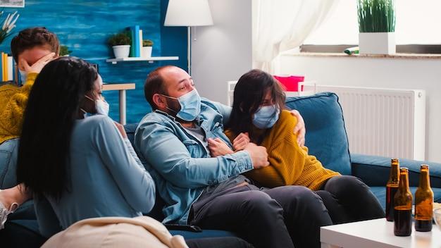 Группа многонациональных друзей смотрит фильм ужасов по телевизору в страхе, проводит выходные вместе в маске для лица, чтобы предотвратить заражение covid 19 во время глобальной пандемии, вызывая отвращение к пиву и чипсам