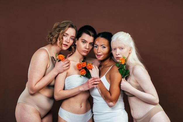 スタジオで一緒にポーズをとるさまざまな種類の肌を持つ多民族の女性のグループ。ボディポジティブと自己受容についての概念