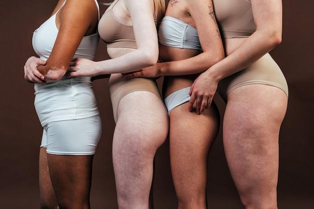 다양한 피부를 가진 다민족 여성들이 스튜디오에서 함께 포즈를 취하고 있습니다. 신체 긍정과 자기 수용에 대한 개념