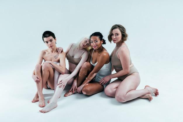 몸에 대한 스튜디오 개념에서 함께 포즈를 취하는 다양한 피부를 가진 다민족 여성 그룹