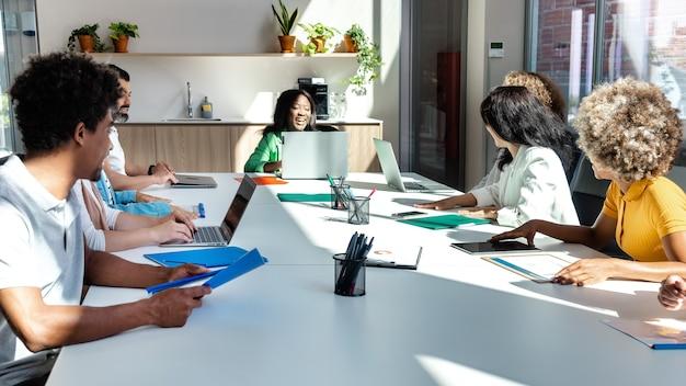 同僚の横のバナー画像を聞いてビジネス会議で多民族の同僚のグループ