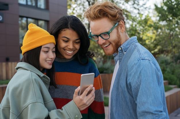 ビデオを見ている携帯電話を使用して多民族の笑顔の友人のグループ