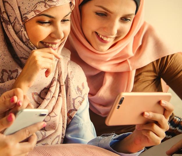 スマートフォンで遊んでいるムスリム女性のグループ