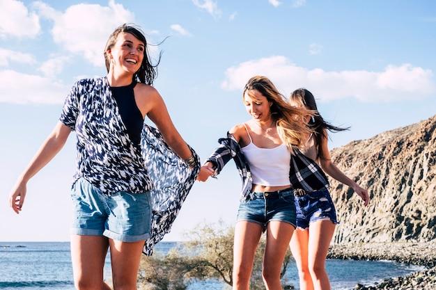 笑顔と笑いを楽しんで友情でビーチの近くを一緒に歩いている素敵な美しい若い女の子のグループ。屋外の自然の自由の場所の概念の友情-休暇と夏の季節
