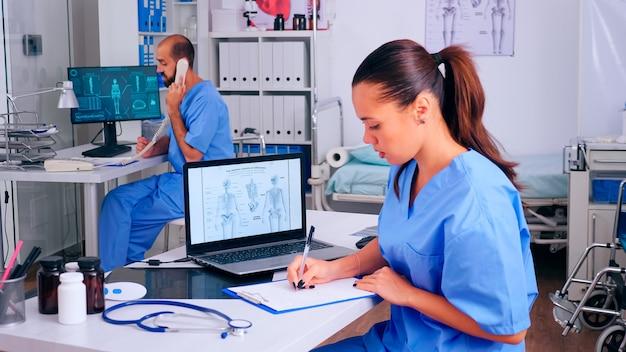 病院のオフィスで働いている看護師のグループで、デジタルの人間の骨格の提示とボディスキャンを分析しています。診察を受け、診断された患者のリストを作成し、解像度を作成する医学の制服を着た医師