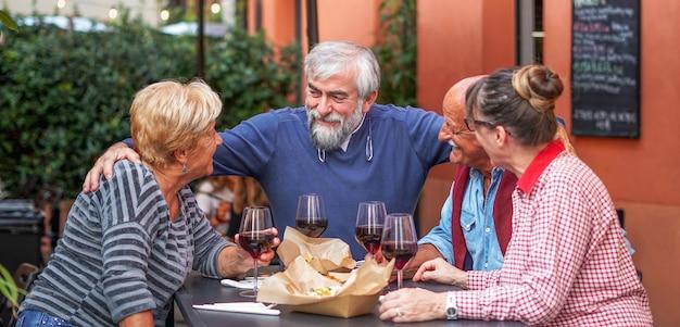 Группа пожилых людей ест и пьет на открытом воздухе -