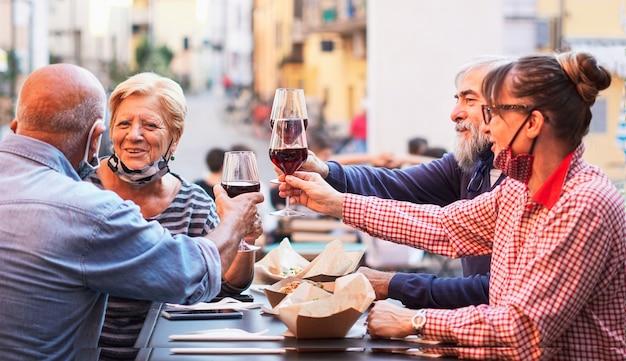 Группа пожилых людей ест и пьет на открытом воздухе