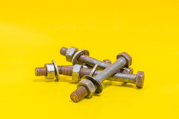 노란색 배경에 오래 된 녹슨 볼트, 와셔 및 너트의 그룹 고정 요소입니다. 스톡 사진