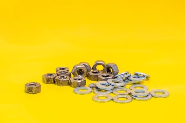 노란색 배경에 오래 된 와셔와 녹슨 너트의 그룹 고정 요소입니다. 스톡 사진