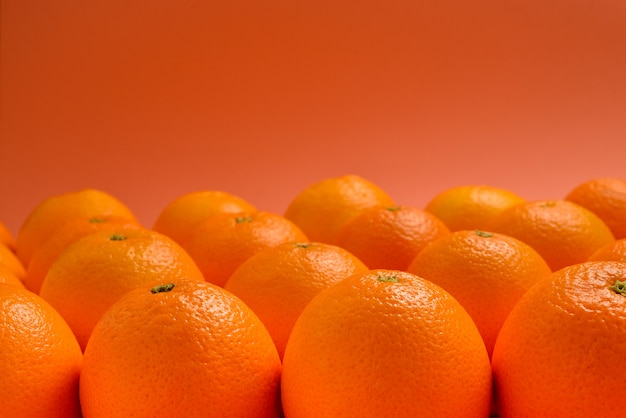 Группа апельсинов в ряд на оранжевом фоне, пространство для текста или дизайна.