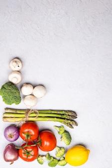 有機の新鮮な野菜のグループ-グリーンアスパラガス、ブロッコリー、灰色の背景にキノコ、フラットレイ。健康的な菜食主義の食糧、食事療法および家庭料理の概念。上面図、コピースペース。