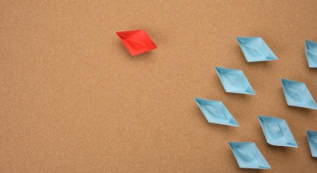 Группа бумажных корабликов на коричневом фоне. концепция сильного лидера в команде, манипулирование массами, поиск новых перспектив, сотрудничество и объединение. запускать