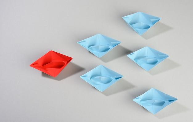 Группа бумажных корабликов на серой поверхности. концепция сильного лидера в команде, манипулирование массами, поиск новых перспектив, сотрудничество и объединение. запускать