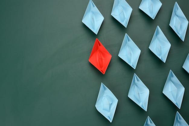 Группа бумажных корабликов на зеленом фоне