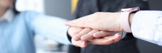 オフィスのクローズアップで手を一緒に折りたたむパートナーのグループ