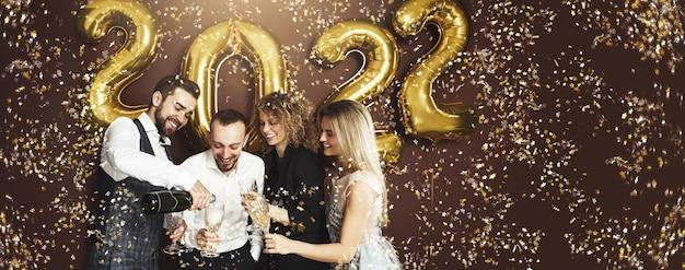 Группа тусовщиков, празднующих приход нового 2022 года с золотыми шарами и падающим конфетти, пьет игристое вино
