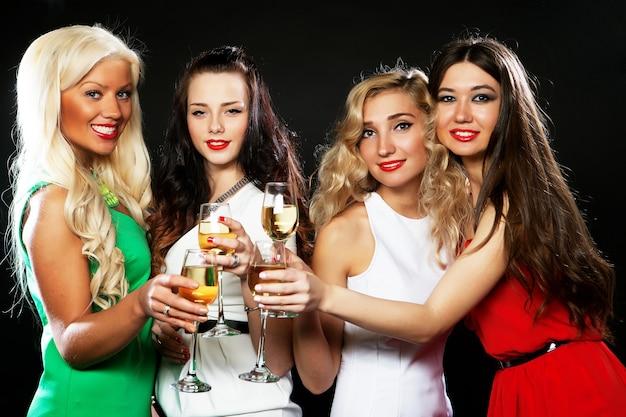 스파클링 와인으로 피리를 부딪 치는 파티 소녀 그룹