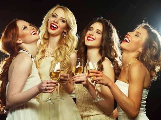 スパークリングワインでフルートをチリンと鳴らすパーティーの女の子のグループ