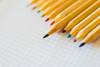 Group of pencils arranged on graph paper.