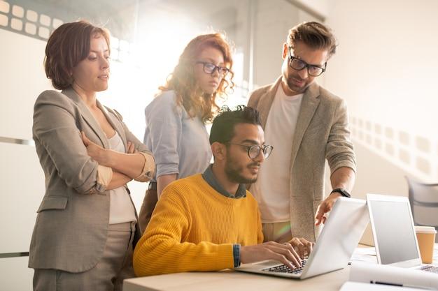 Группа задумчивых креативных рекламодателей, стоящих за столом и просящих веб-дизайнера добавить элементы дизайна для презентации в офисе