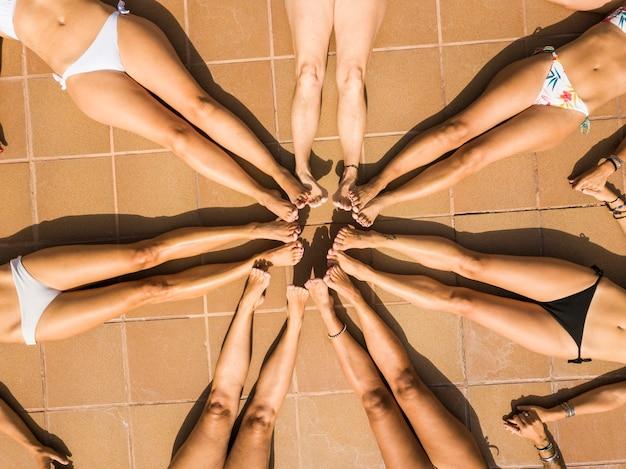 人々のグループビキニの女の子の関係体は上から見た星を構成します-一緒に友情の概念と女性の友人のための夏休みの休暇の楽しみ-日焼けした肌のための屋外の日光浴