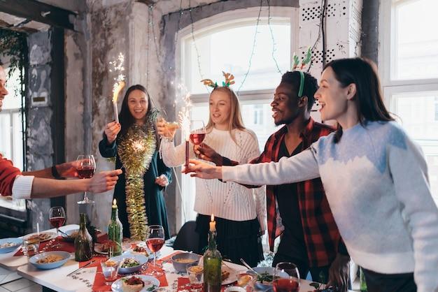 크리스마스 또는 새해 전날을 축하하는 사람들의 그룹입니다. 술을 건배하고 함께 저녁을 즐기는 친구들.