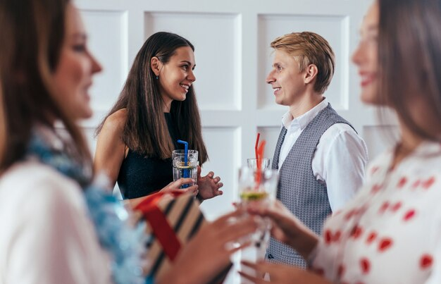 Группа людей празднует, разговаривает, пьет коктейли.