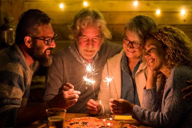 Группа людей, празднующих новый год 2021 года после тяжелого 2020 года - концепция до свидания 2020 - семья веселится и веселится вместе с бенгальскими огнями дома, едят пиццу за ужином - концепция christimas