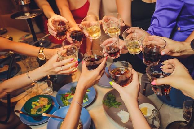 パーティーでグラスをチリンと鳴らす人々のグループ