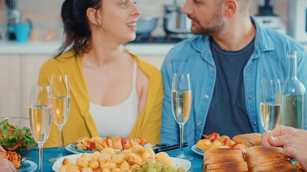 夕食時に白ワインのグラスをチリンと鳴らしながら、キッチンのテーブルの周りに座っている人々のグループ。多世代、4人、グルメな食事の間に話したり食べたりする2人の幸せなカップル、en