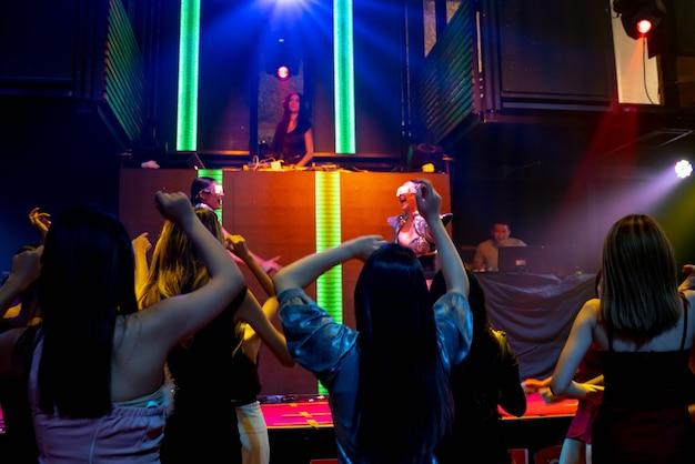 무대에서 dj의 음악 비트에 맞춰 디스코 나이트 클럽에서 춤을 추는 사람들
