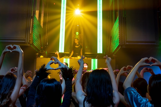 Группа людей танцует в ночном диско-клубе под музыку ди-джея на сцене